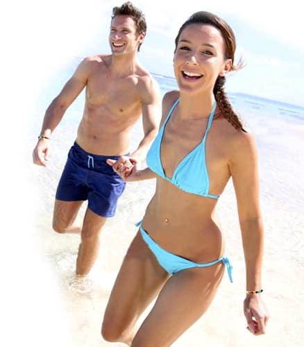 Couple heureux sur la plage avec bracelets énergie